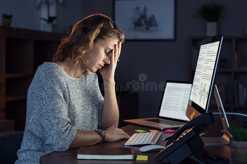 Beklemtoonde vrouw die na verloop van tijd bij nacht werken stock afbeeldingen