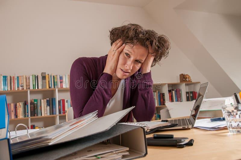 Beklemtoonde vrouw in het bureau stock afbeelding