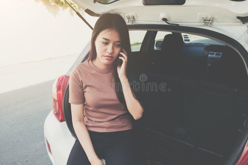 Beklemtoonde vrouwenzitting en het gebruiken van celtelefoon voor assistancenear w royalty-vrije stock foto