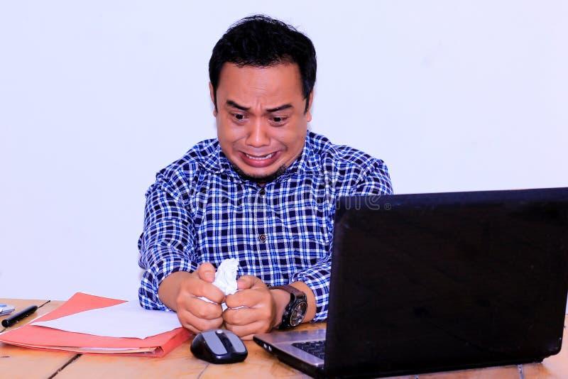 beklemtoonde zakenman die met documenten en grafieken bij lijst in bureau zitten stock fotografie