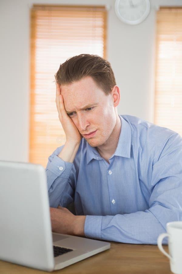Beklemtoonde zakenman die zijn laptop bekijken royalty-vrije stock afbeelding