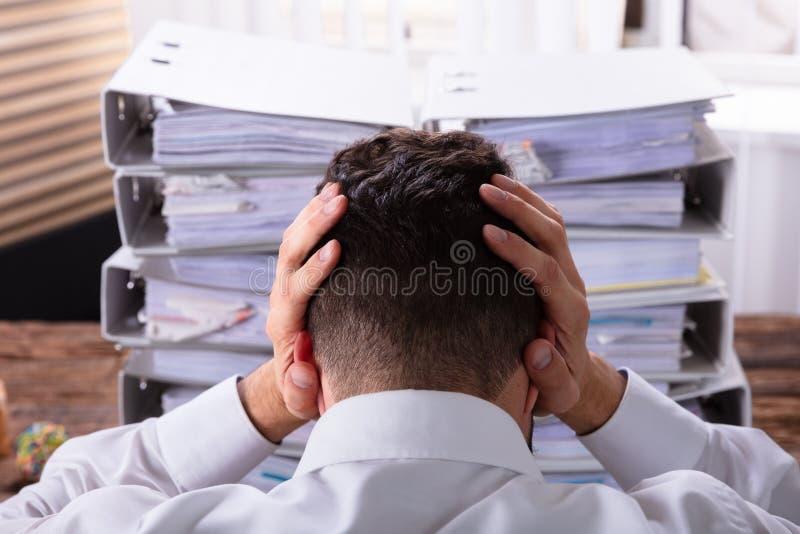 Beklemtoonde Zakenman In Front Of Stacked Folders stock afbeelding