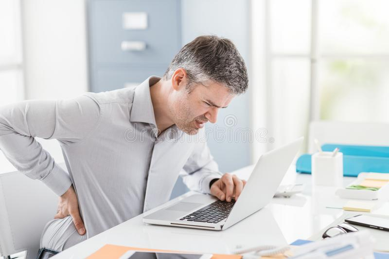Beklemtoonde zakenman met rugpijn, werkt hij bij bureau en masseert zijn rug stock fotografie