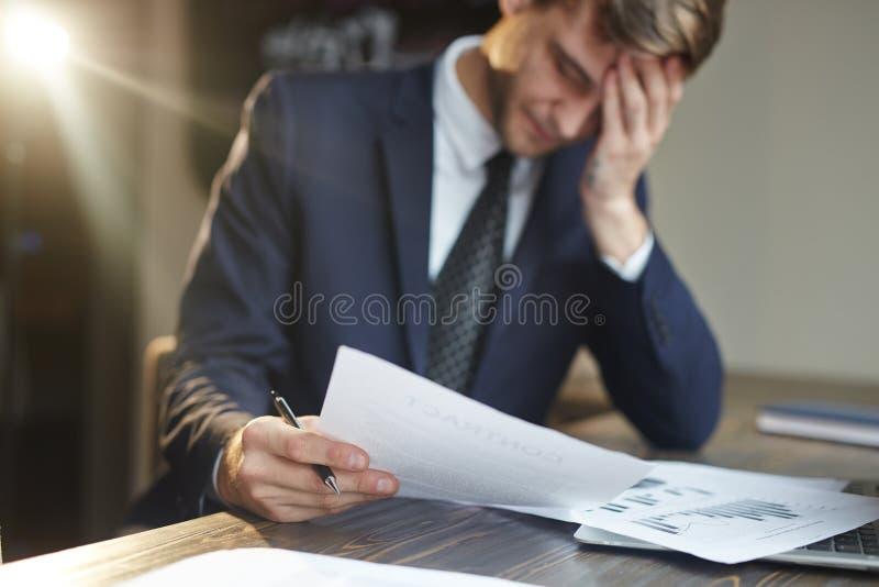 Beklemtoonde Zakenman Working met Financiële Documenten stock foto
