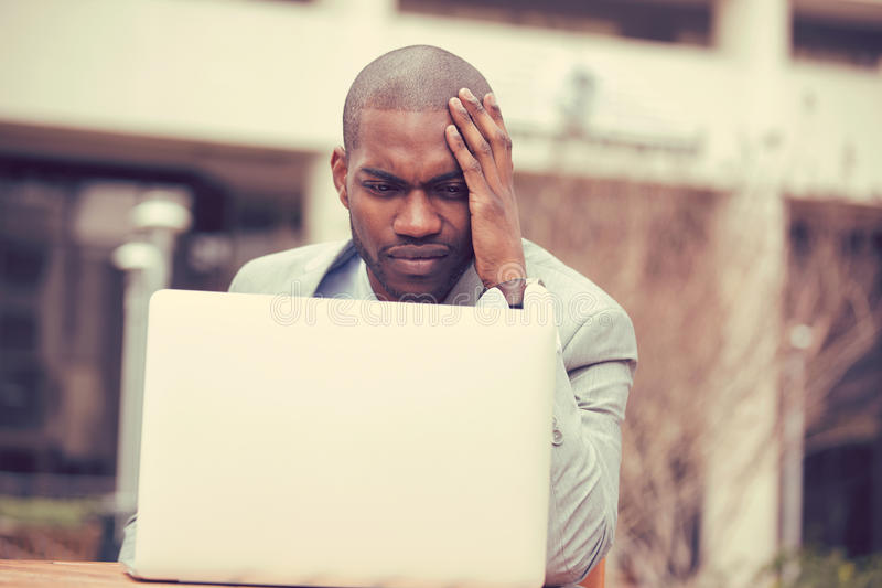 Beklemtoonde zakenmanzitting buiten collectief bureau die aan laptop werken stock afbeeldingen