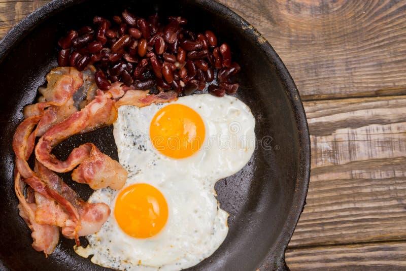 Bekon, jajko i fasola, Solony jajko i kropiący z czarnym pieprzem Angielski śniadanie Piec na grillu bekon, dwa jajka i fasole w  obraz royalty free