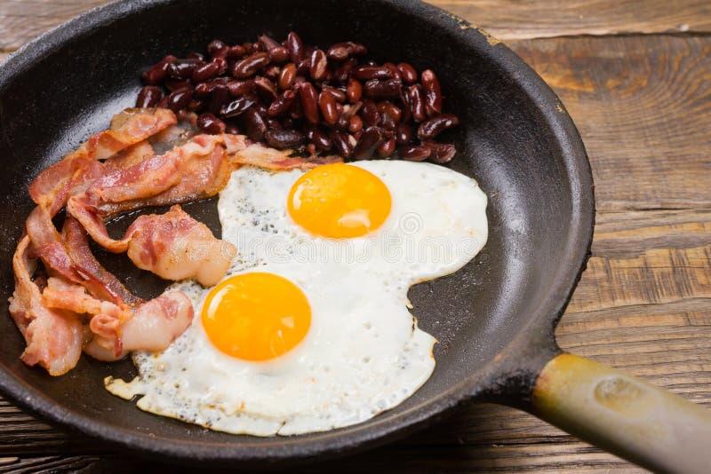 Bekon, jajko i fasola, Solony jajko i kropiący z czarnym pieprzem Angielski śniadanie Piec na grillu bekon, dwa jajka i fasole w  fotografia royalty free