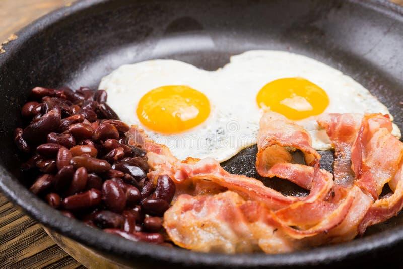 Bekon, jajko i fasola, Solony jajko i kropiący z czarnym pieprzem Angielski śniadanie Piec na grillu bekon, dwa jajka i fasole w  obrazy royalty free