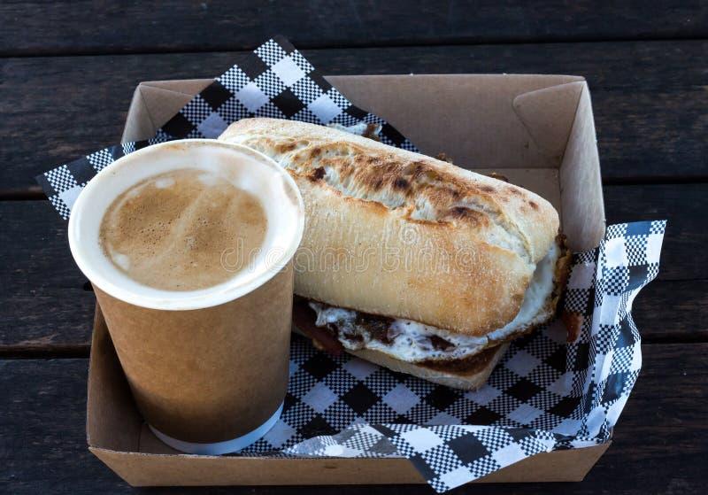 Bekonowa i jajko śniadaniowa ciabatta rolka z bierze oddaloną kawę z w kratkę serviettes w pudełku fotografia royalty free