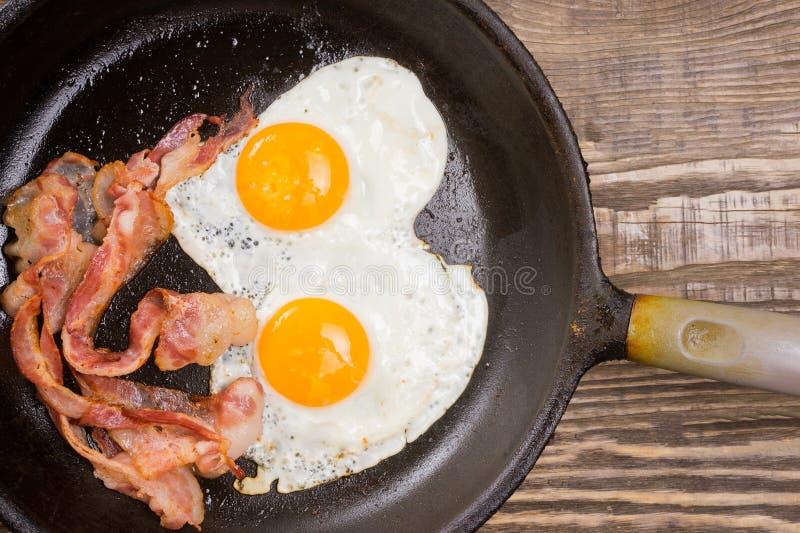 Bekonowy i jajko Solony jajko i kropiący z czarnym pieprzem Angielski śniadanie Piec na grillu bekon, dwa jajka na niecce na drew obrazy stock