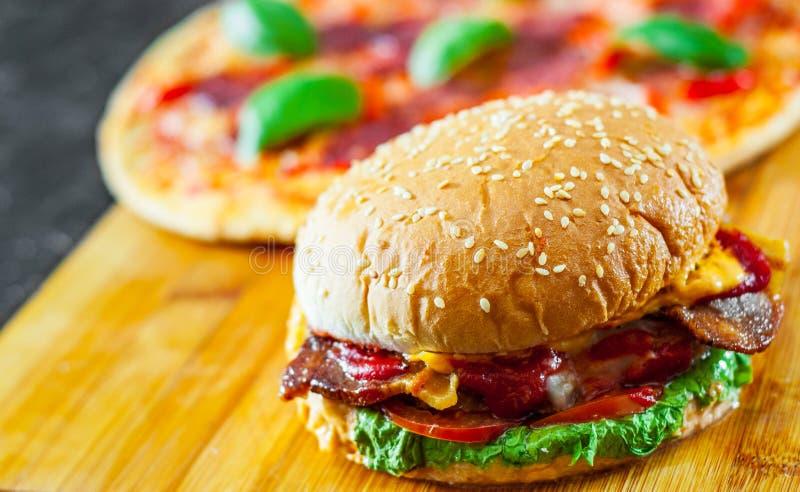 Bekonowy serowy hamburger z wołowina pasztecika pomidorową cebulą i pizzą z mozzarella serem, baleron, pomidory, salami, pieprz,  obraz stock