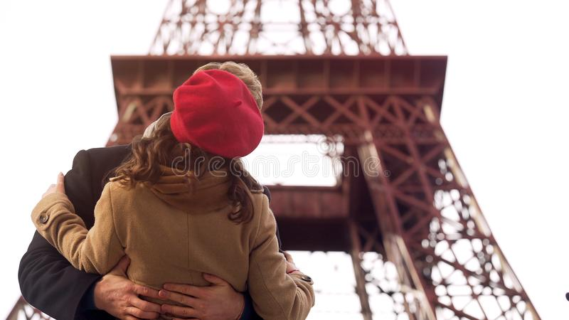 Bekoorde man die passionately geliefde vrouw op romantische datum in Parijs kussen stock foto