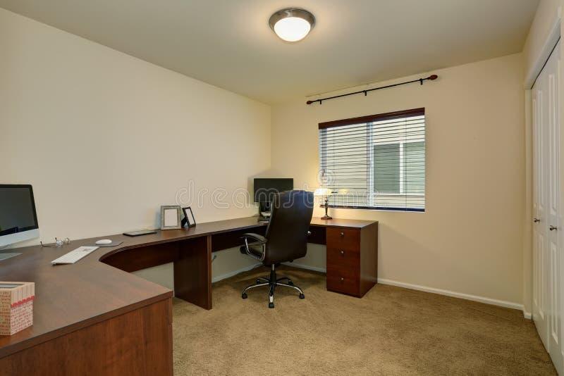 Bekväm inrikesdepartementetinre med det stora bruna skrivbord- och mattgolvet royaltyfri foto