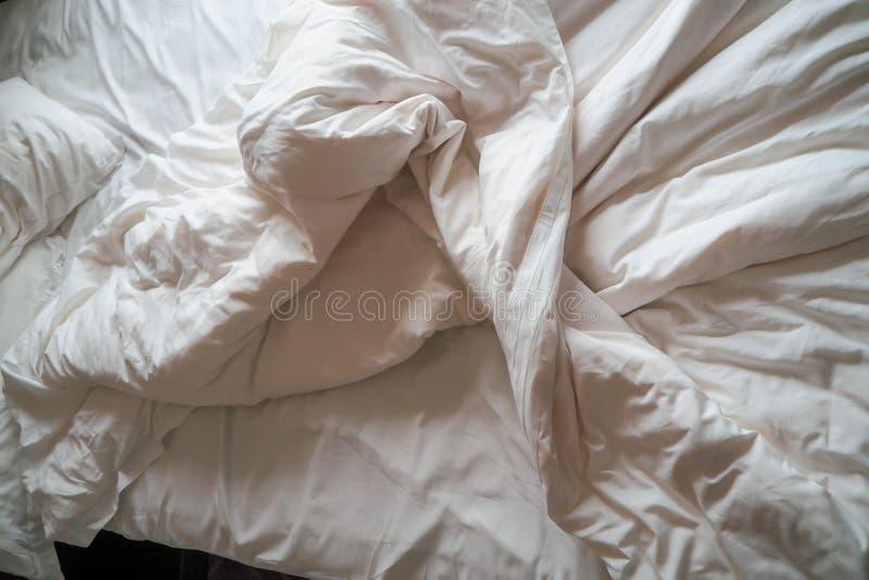 Bekväm säng med smutsig vit linne Vit kudde med filten på ogjord säng Begrepp av att koppla av efter morgon arkivfoto