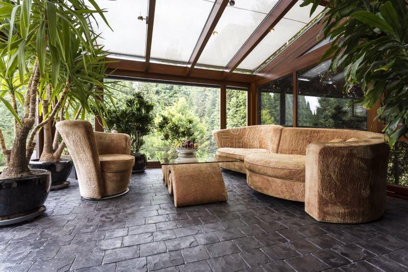Bekväm vardagsrumuppsättning i drivhus arkivfoto