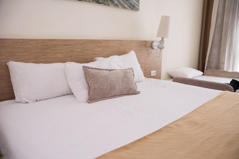 Bekväm vit säng stor badroominre Utvalt fokusera arkivbild