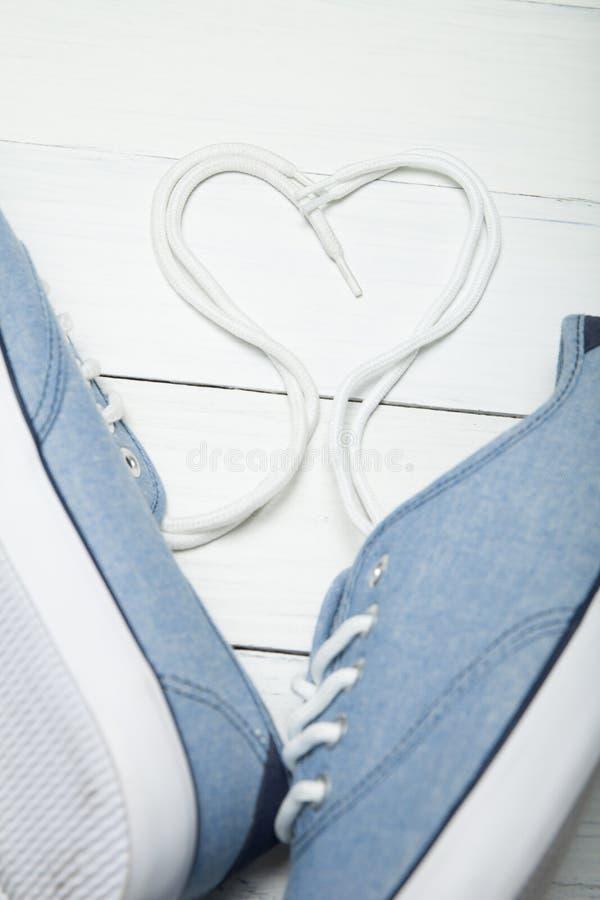 Bekväma tillfälliga skor, hjärta gjorde av vit snör åt på en träbakgrund royaltyfri bild