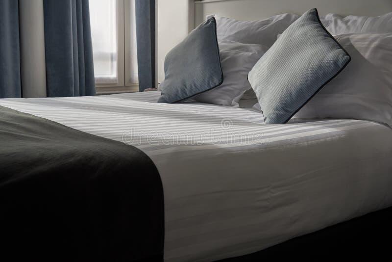 Bekvämt sovrum och solljus i morgonen royaltyfri bild