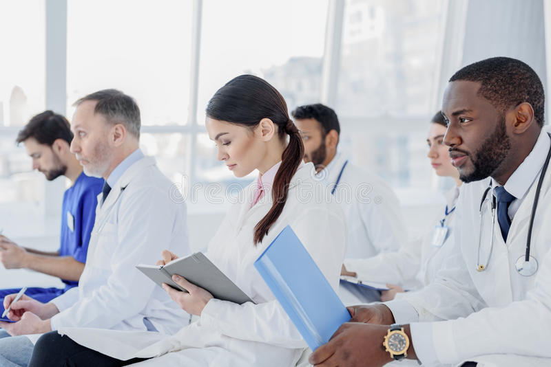 Bekwame artsen die aan medisch rapport luisteren royalty-vrije stock fotografie