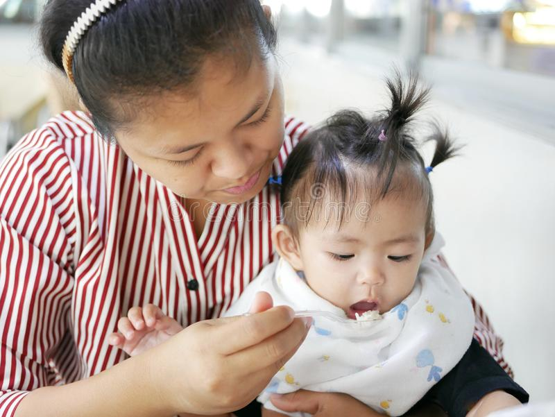 Bekwame Aziatische moeder die kleine lepel gebruiken om haar babymeisje, 12 maanden oud, bij een cafetaria te voeden royalty-vrije stock foto