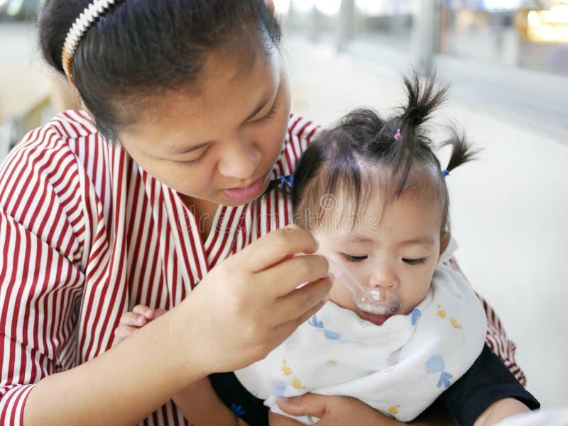 Bekwame Aziatische moeder die kleine lepel gebruiken om haar babymeisje, 12 maanden oud, bij een cafetaria te voeden royalty-vrije stock afbeeldingen