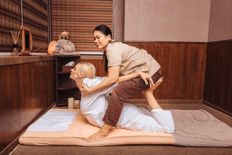 Bekwame Aziatische vrouw die massage voor haar cliënt doen royalty-vrije stock afbeelding