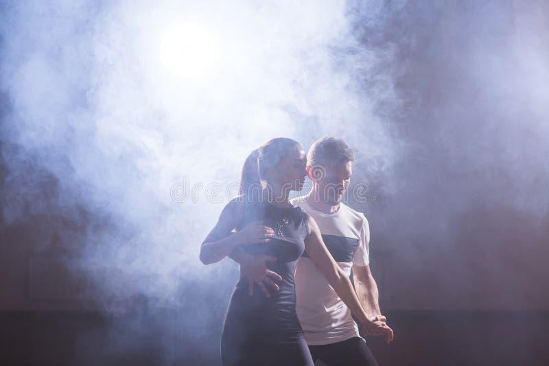 Bekwame dansers die in de donkere ruimte onder het de overleglicht en rook presteren Sensueel paar die artistiek uitvoeren stock foto
