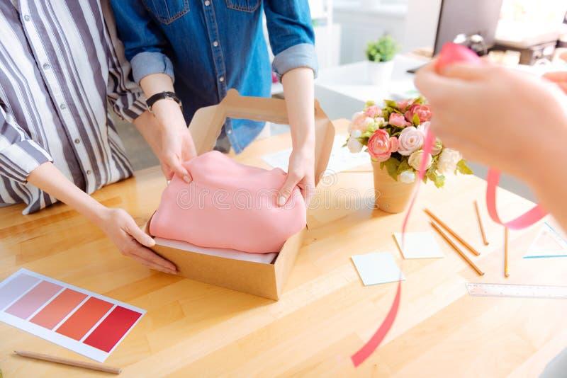 Bekwame kleermaker die roze doek zetten in doos stock foto's