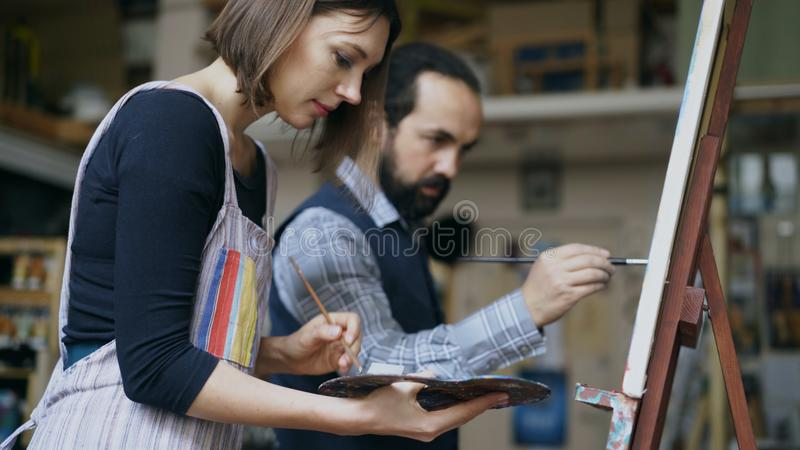 Bekwame kunstenaarsman die het jonge vrouw schilderen op schildersezel onderwijzen bij kunstacademiestudio - creativiteit, onderw stock foto