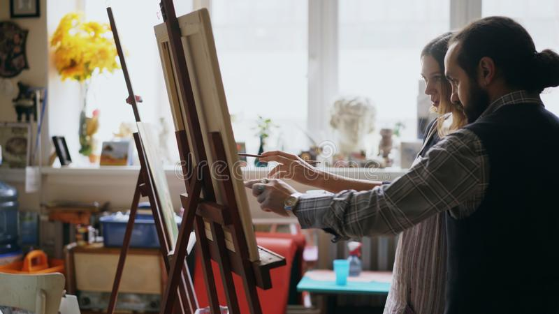Bekwame kunstenaarsmens die jong meisje onderwijzen aan het trekken van schilderijen en het verklaren van de grondbeginselen in k stock afbeeldingen