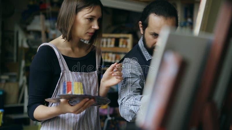 Bekwame kunstenaarsmens die jong meisje onderwijzen om schilderijen te trekken en de grondbeginselen in kunststudio verklaren stock afbeelding