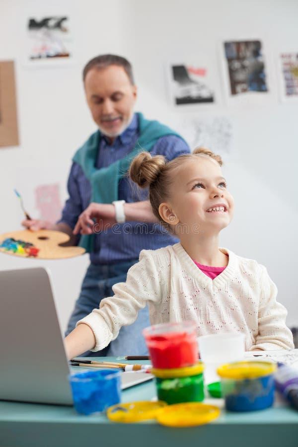 Bekwame rijpe schilder en zijn kleine kleindochter stock foto