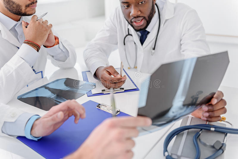 Bekwame traumatologists die röntgenfoto van menselijk been bespreken stock foto