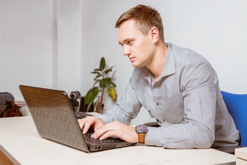Bekymmeraffärsman som använder bärbara datorn, medan sitta i regeringsställning Arbetare som skriver emailen på datoren royaltyfri fotografi
