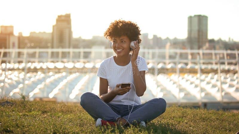 Bekymmerslös afro--amerikan kvinna som lyssnar till musik i hörlurar och tycker om ungdom royaltyfri foto