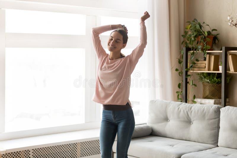 Bekymmerslös attraktiv flickadans i vardagsrum hemma arkivfoton