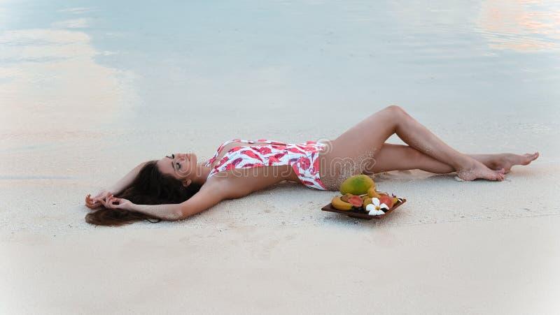 Bekymmerslös brunettkvinna som ligger på vit sand som tycker om liv på den tropiska stranden Sexig bikinimodell med exotiska fruk arkivbild