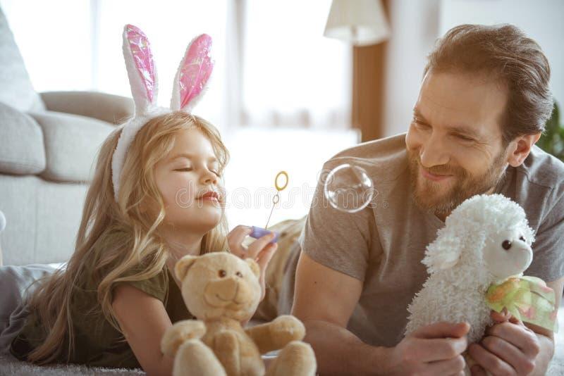 Bekymmerslös flicka som har gyckel med hennes hemmastadda pappa royaltyfria foton