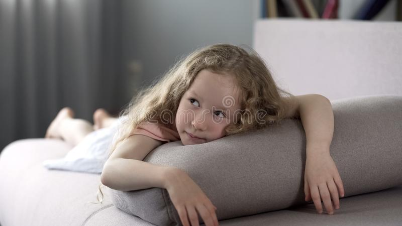 Bekymmerslös flicka som ligger på lagledaren och drömmer om ny leksaker, lycklig barndom arkivfoton