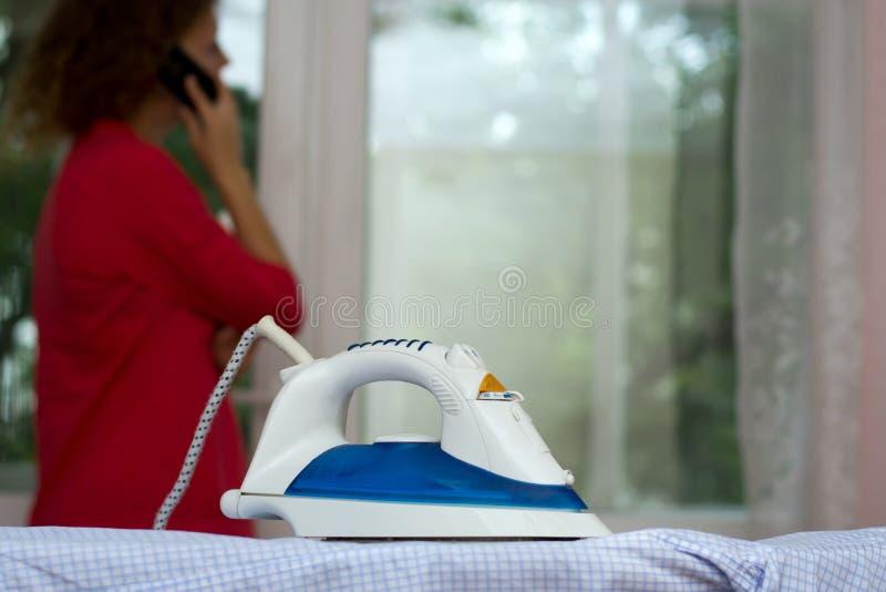 Bekymmerslös flicka som talar på telefonen som glömmer om järnet på strykbrädan royaltyfria bilder