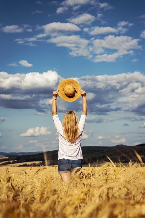 Bekymmerslös kvinna för blont hår som bär tillfälliga kläder mot härlig himmel arkivfoto