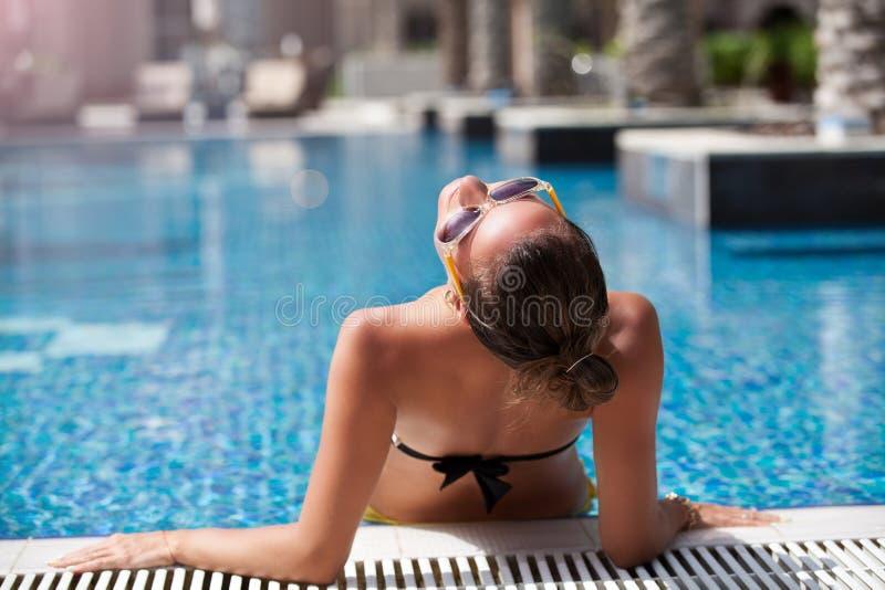 Bekymmerslös kvinna för sommarsemester som kopplar av i simbassäng royaltyfri foto