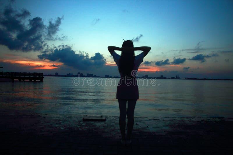 Bekymmerslös kvinna i solnedgången vid Dishui sjön i Shanghai, sunt bosatt begrepp, ren lycka och frihet royaltyfria foton
