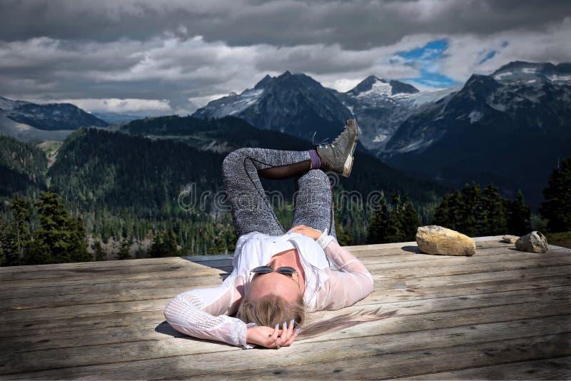 Bekymmerslös kvinna som ner ligger på tältblocket, når att ha fotvandrat dag arkivbilder