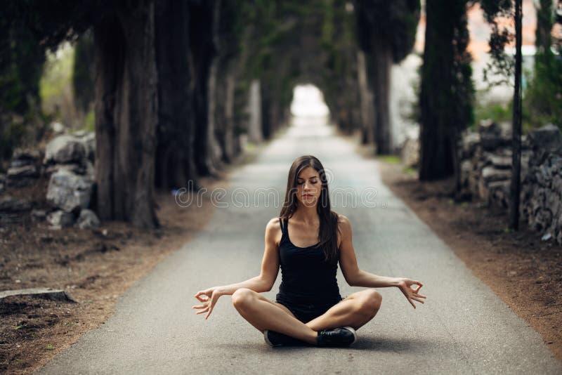 Bekymmerslös lugna kvinna som mediterar i natur Finna inre fred Man att göra hälften som viker i sittande lotusblommapos Andlig l fotografering för bildbyråer