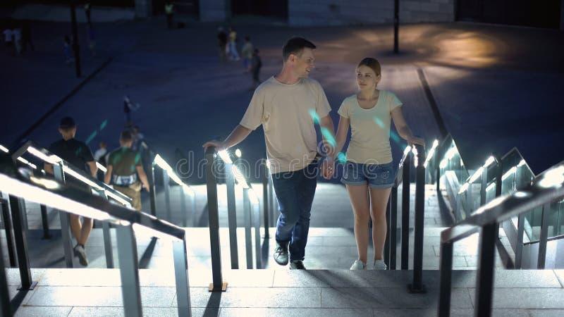 Bekymmerslösa par som uppför trappan går för att hålla ögonen på den upplysta nattstaden, romantiskt datum arkivbild