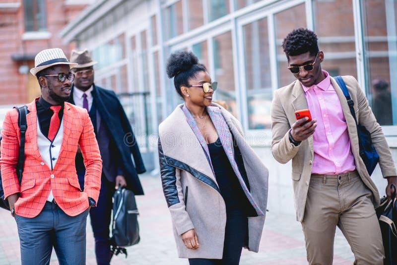 Bekymmerslösa studenter som tycker om passera tiden tillsammans i gatan fotografering för bildbyråer