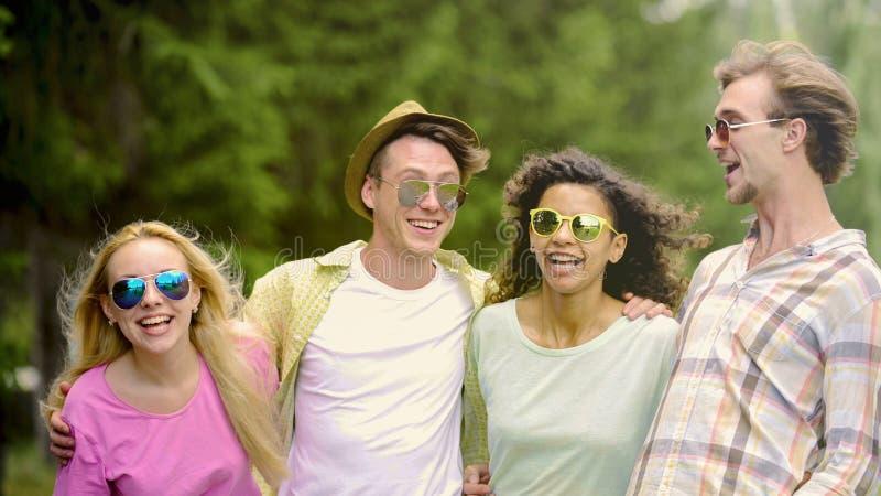 Bekymmerslösa vänner som kramar och skrattar, bra tid i, parkerar tillsammans, kamratskap arkivbild