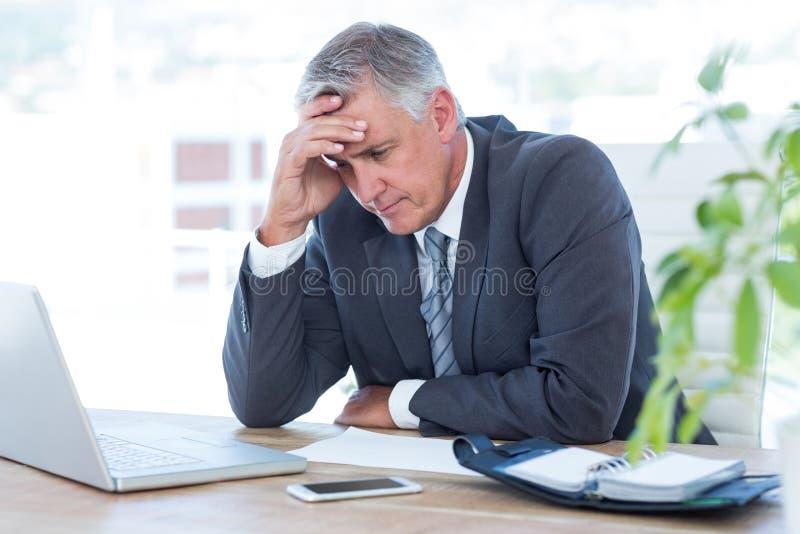 Bekymrad affärsman med huvudet i en hand royaltyfri foto