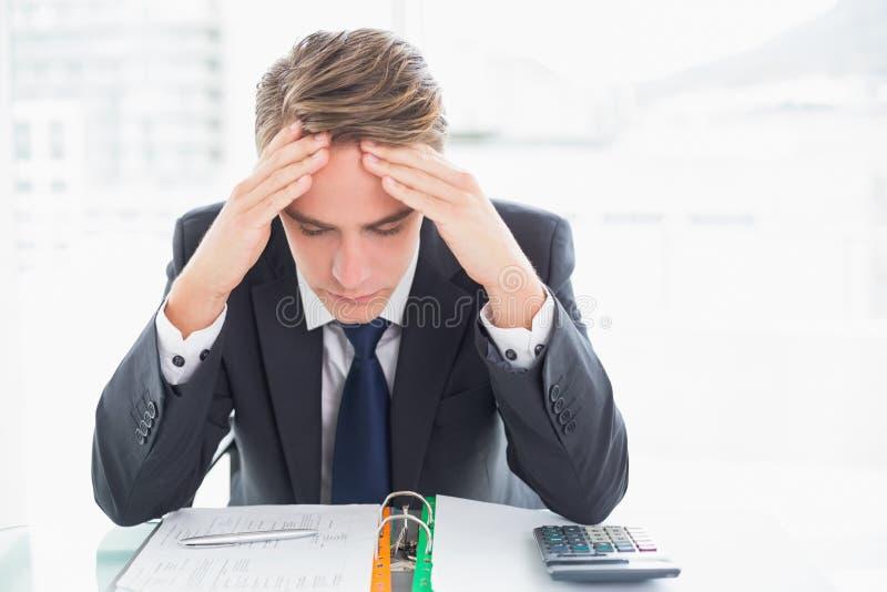 Bekymrad affärsman med huvudet i händer på kontorsskrivbordet royaltyfri bild